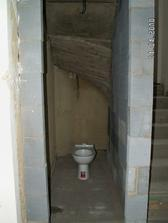 záchod dole pod schodama, ale ještě za ním budou vyzděný skříňky a přijde k němu i umyvadlo