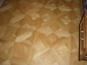 Detail podlahy. Sú originál lepené, drevené, dubové parkety, tri krát brúsené a lakované.