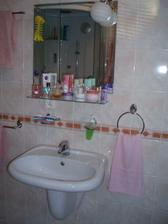 Oproti umývadlu je sprchový kút, je menený tento rok a výmena čaká aj umývadlo s batériou. Malá renovácia po desiatich rokoch. Pri stavbe neboli korunky nazvyš, tak sa už sanita mení za kvalitnejšiu.
