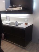 tmava kuchyn, bila deska z corianu vytazena az k desce na stene