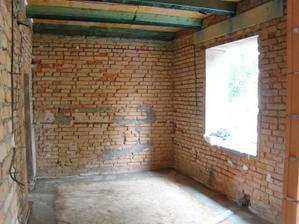 Část obýváku, do které se vstoupí z předsíně. Na celé protější zdi bude zděná knihovna obložená umělým kamenem. Hned zde po pravici za zdí bude psací stůl s pc.