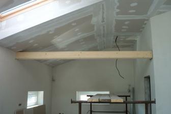 Takýmto trámom sme opticky predelili kuchyňu s obývačkou - budú z neho visieť svetlá nad barový pult