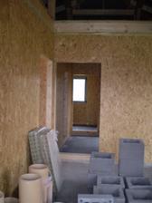 sme v obývačke a vidíme do chodby kde sú izby a kúpeľňa. Materiál na komín je prichystaný.