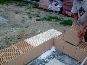Prvý rad tehly sa zasýpa drveným polystyrénom...