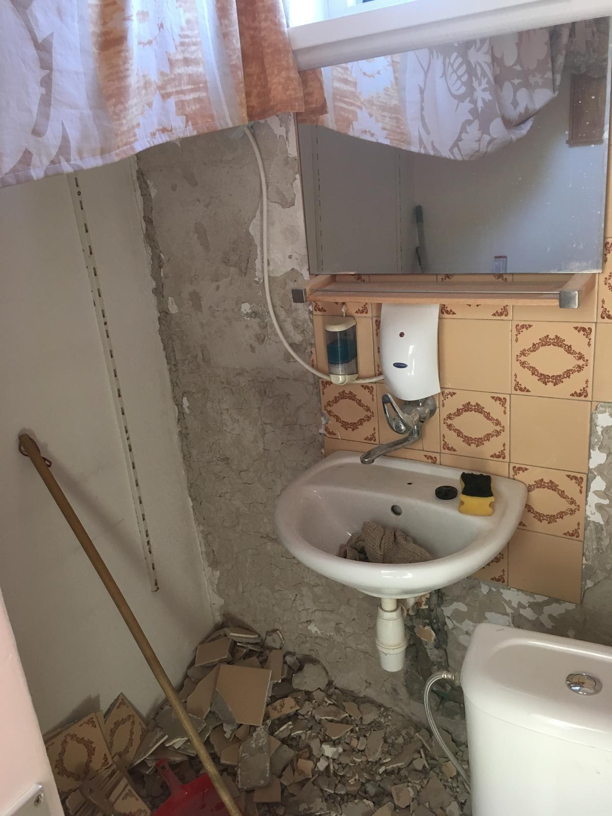 Rekonštrukcia WC - Aj zrkadlo to prežilo. Obklad pomaly mizne.