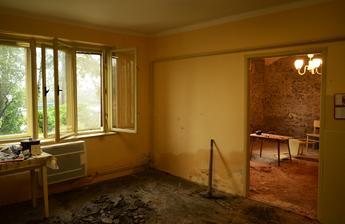 Kuchynka s hnilou podlahou, vlhkou stenou a otlčenou obývačkou