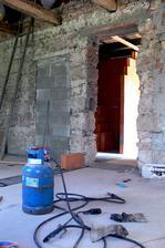 jedny dvere zamurované, druhé vybúrané a prvá tehla na kutici č. 2