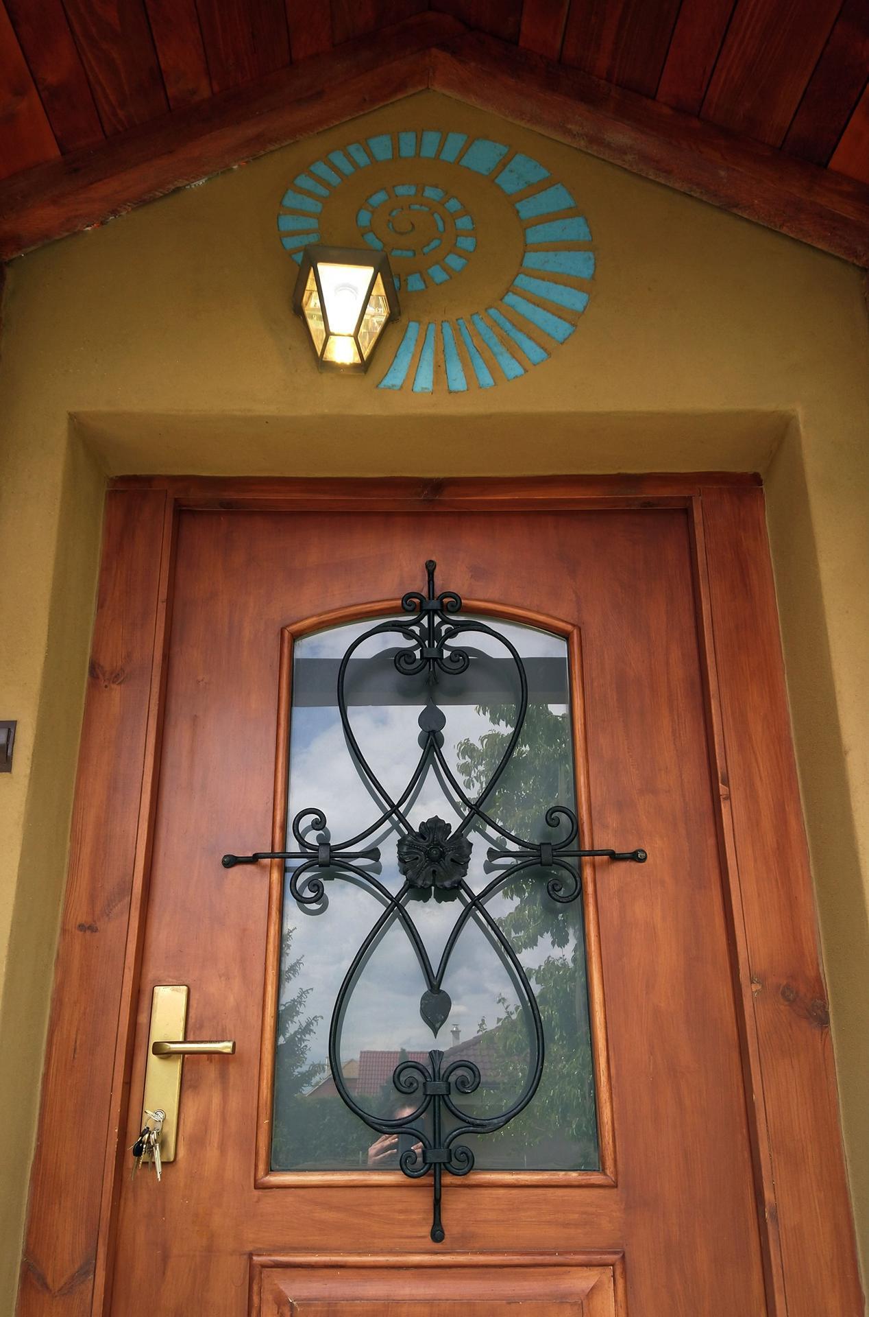 """Hlinené omietky - Hlinené sgrafitto nad vchodom. Vačšina ludí by dala lampu presne do stredu nad dvere, ale elektrikár bol """"umelec"""". Čo už, špirála trochu opticky odvadza  pozornosť od krivej lapmy."""