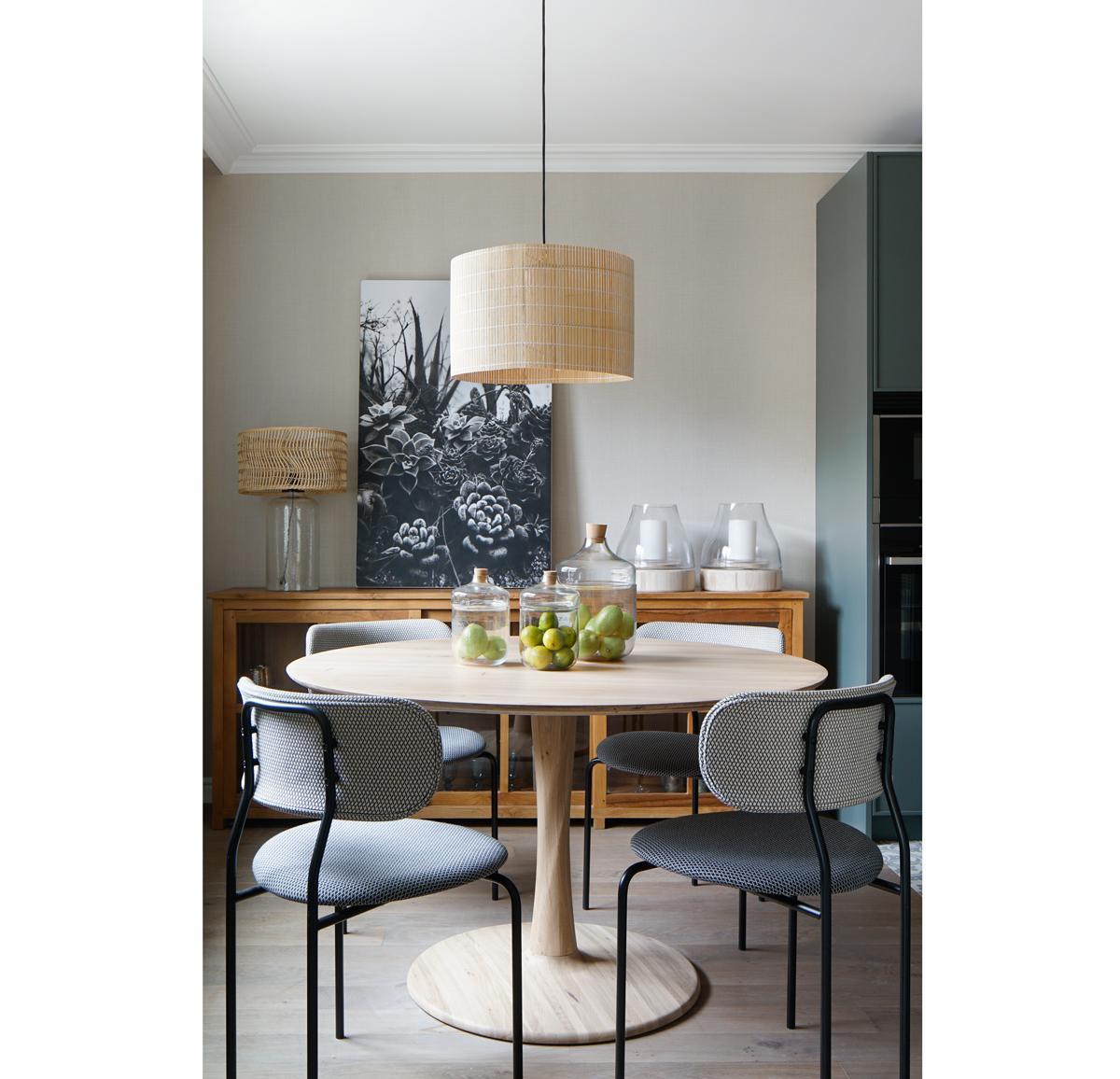 Elegantné retro bývanie v historickej budove Barcelony - Jedáleň je od kuchynskej časti vizuálne oddelená podlahou. Kým v kuchyni nájdeme kachličky, v jedálni sa nachádza drevená podlaha. Čierna kuchynská linka a ostrovček sú zjemnené stolom z javorového dreva, komodou z masívu a osvetlením z bambusu a rat
