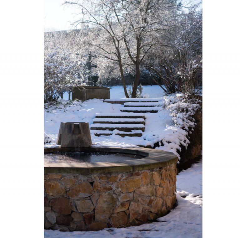 Návšteva pamiatkovo chránenej storočnej záhrady - Kamenná kruhová fontána dokonale ladí s exteriérom vily. Pôvodná liatinová pumpa na vodu, i keď dostala nový náter, je spomienkou na časy minulé.