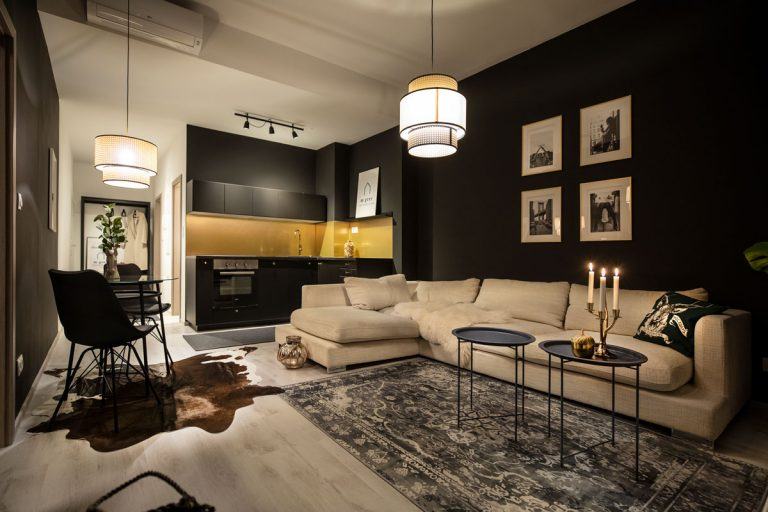 Vstúpte do interiéru, kde si prvé husle zahrali zlato a čierna - Čiernobiele fotografie v decentných zlatých rámoch na bielom podklade stoja v rafinovanej opozícii k čiernej stene.