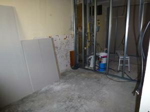Keďže pôvodné priečky neboli murované, bez povolenia statika sa nesmú murovať ani nové priečky - preto padla voľba na sadrokartón, začali sa ťahať profily na uchytenie sadrokartónu. Pohľad z prechodu z obývačky do kuchyne, vzadu je jadro. Táto stena