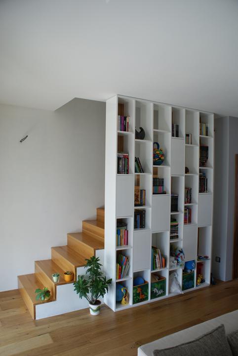 Návrh a realizácia interiéru bytu - Knižnica čiastočne plní aj funkciu zábradlia a niektoré chrbáty sú sklenené aby prepúšťali na schodisko čo najviac svetla