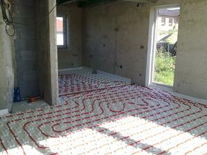 Pohled z obývacího pokoje do kuchyně, u okna po zem bude stůl, vlevo ten výklenek je prostor pro krb.