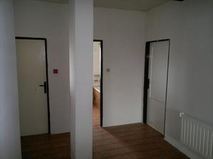 Úplně vlevo (není vidět) vstup do ložnice, vlevo wc, za sloupkem koupelna a vpravo budoucí dětský pokoj, koupelna přijde rozšířit až ke sloupku