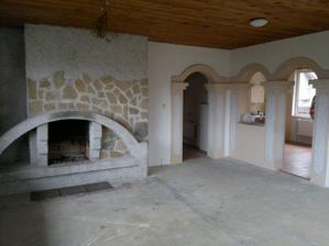Obývací pokoj, vedle krbu vstup z chodby a vpravo a průchod z obýváku do kuchyně