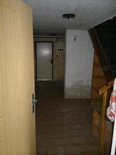 Vstup do domu, spodní chodba, naproti dveře do budoucí prádelny a napravo schody do obytného patra