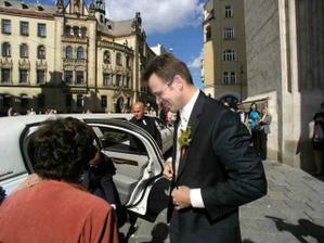 šťastný ženich čeká výstup nevěsty z limuzíny