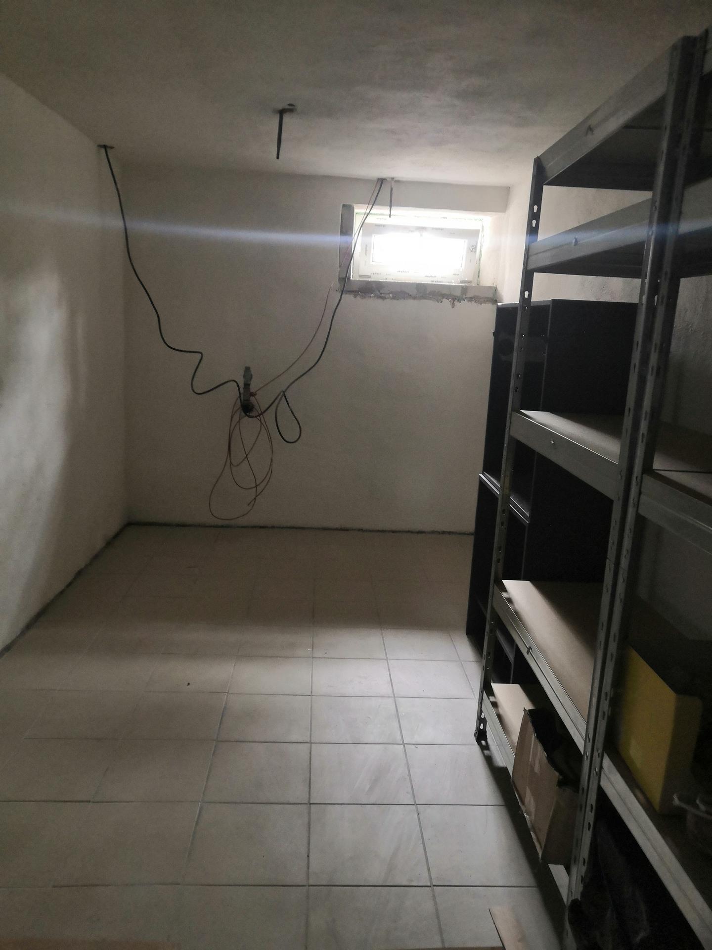 Suterén - Vymalovaná a vydlážděná menší místnost, postavené regály na provizorní sklad.