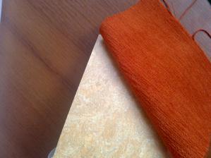 Tmavý je nábytek a oranžová látka sedačky