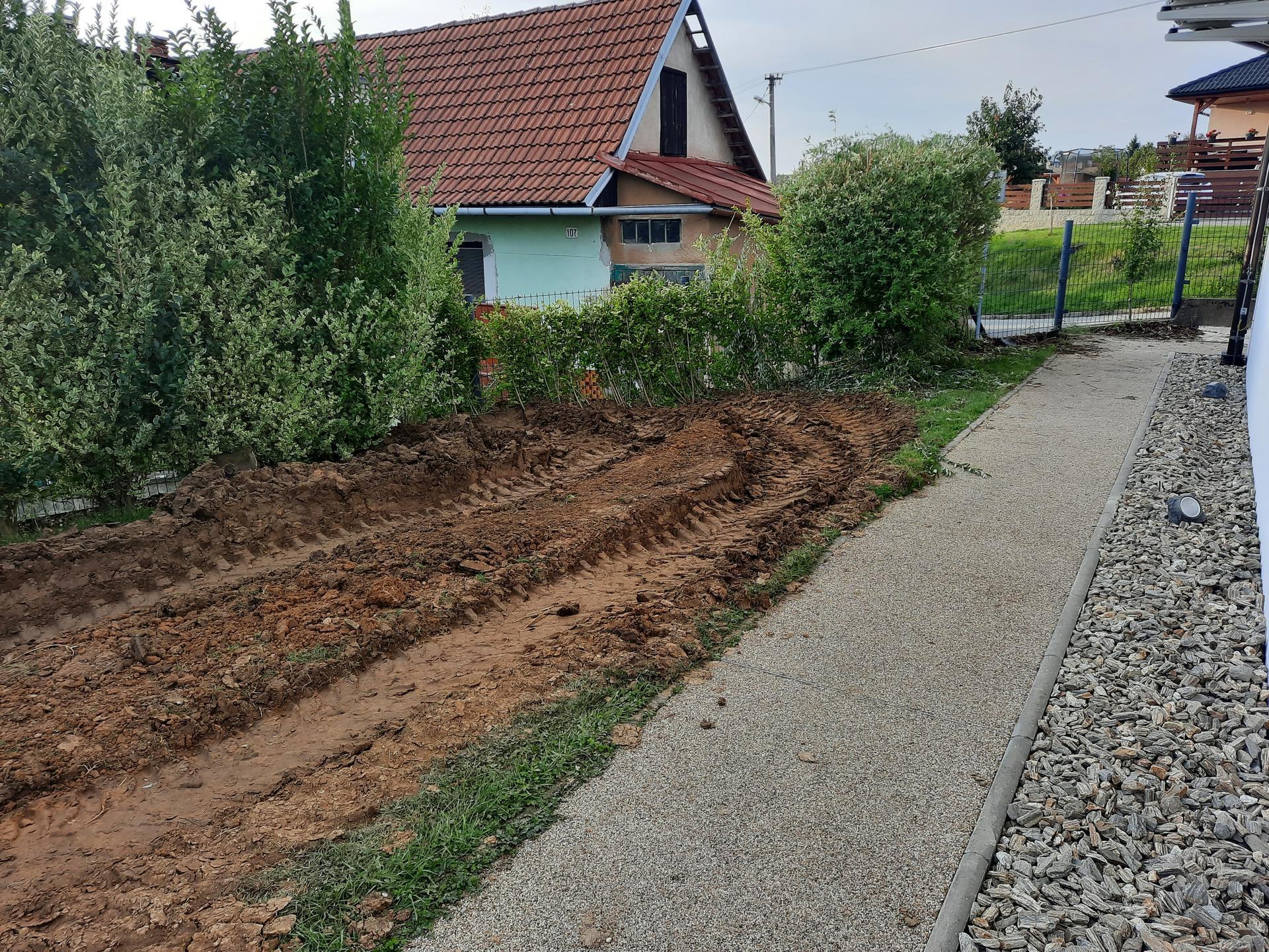 Akce BAZÉN - Dům je umístěn nešťastně a není moc kudy tudy. Druhý bagr vozí vybagrovanou hlínu k plotu, pod nímž stojí náklaďák.