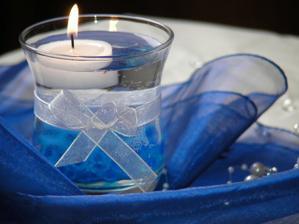 Dekorace - svíčka s vodou (budou v ní kamínky a květ orchideje) a pouze s mašličkou. Pro upozornění, pokud se dávají klasické čajové svíčky, tak se objeví ve skleničky zrezlé fleky, proto je potřeba opravdu koupit svíčky plovoucí.