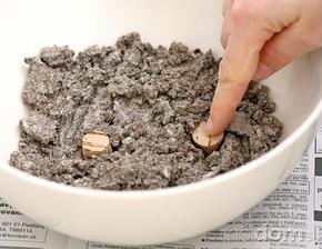 Trocha zmesi dajte na dno plastovej misky a zatlačte do nej dve korkové zátky.