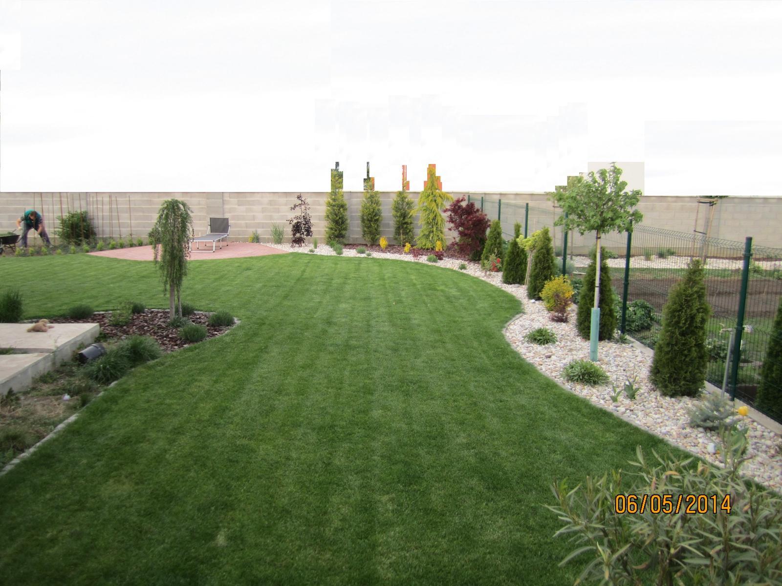 Bývame a dokončievame - pohlad od terasky..zahrada ma necely rok..... cast nalavo sa bude robit, rozsirovat beton o pol metra. preto tam je hlina...