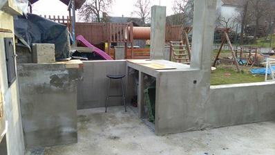 vlevo udírna aa zakrytá pec, naproti pece odkladná plocha- pracovní stůl a pod ním místo na skříňku a lednici