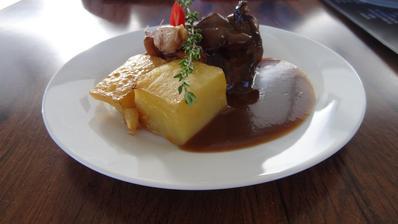 Grilovaný hovězí steak z naší vyzrálé květové špičky Black Angus, podávaný s kachními foie gras, glazovanými liškami a česnekovým konfitem, burgundská omáčka, pečené bramborové fondány
