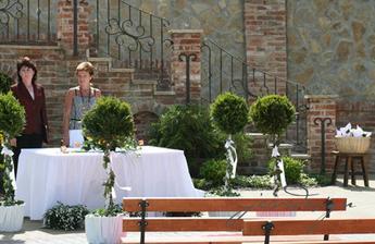 venkovní výzdoba a paní oddávající s matrikářkou. vlevo košíček s kornouty na rýži a okvětní plátky