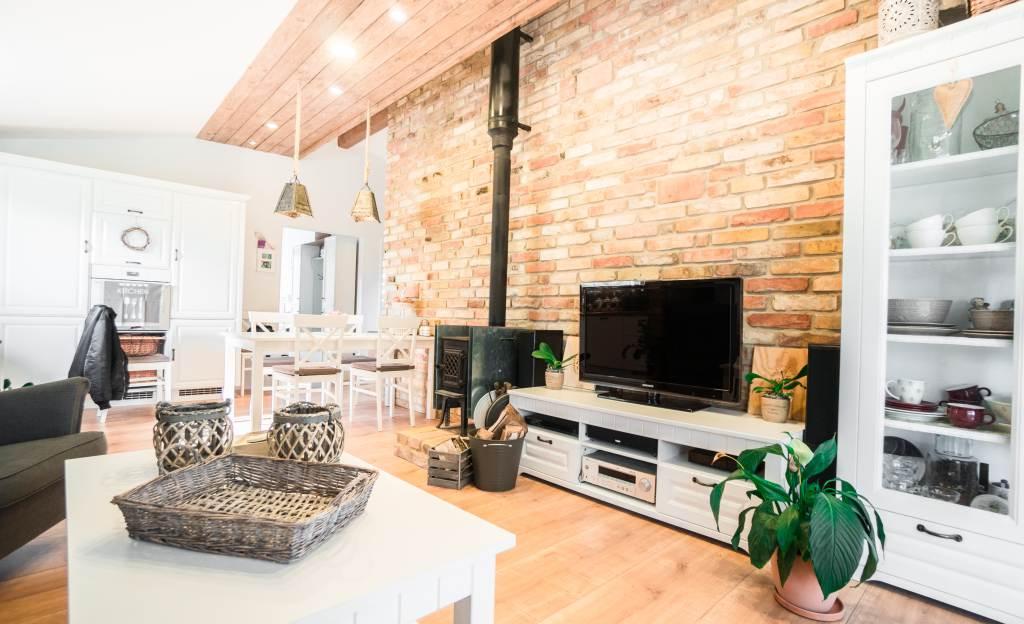 Z typovej drevostavby originál - Stredom domu vedie stena z fermacellu, ktorá oddeľuje dennú zónu od spální. S pomocou tehlárov ju obložili originálnymi starými tehlami narezanými na požadovaný rozmer. Je to výrazná dekoračná dominanta v interiéri, ale zároveň aj akumulačný prvok.