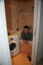 Můj muž při zapojování pračky. Zatím se usmívá, ale byla z toho šílená hádka a pračku nakonec přišel zapojit jeho táta :-)