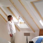 Drevené strešné okno Solstro v spálni s bielou zatemňovacou roletou