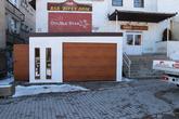 Montovaný oceľový sklad s garážovou bránou Hormann a bočnými oceľovými dverami Hormann LPU40 vo farbe zlatý dub