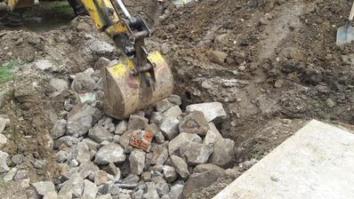Veeeeľká jama trativodu zasypaná kameňmi.