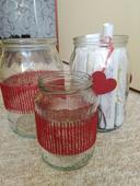 Sklenice/vázy zdobené červenou jutovou stuhou,