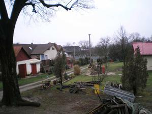 Pohľad z terasy k ceste: cesta je vzadu pri tom sivom plechovom plote, tie dve kolaje su susedova prijazdova cesta, nasa bude hned vedla oddelena plotom