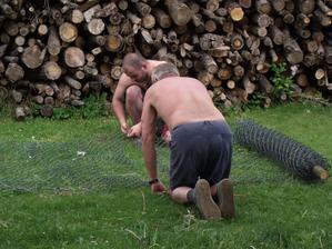 manžel s taťkou přemotávají a opravují pletivo na plot