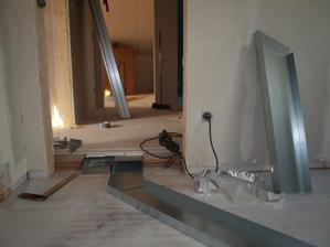 Pohled do horní haly z pokoje, kde právě probíhá montáž rozvodů v podlaze.