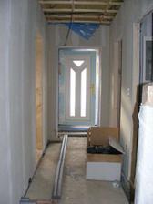 pohled z obýváku přes chodbu na vchodové dveře - zevnitř bílé, z venku zlatý dub