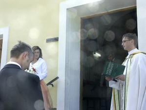 pan farář nás vítá před kostelem