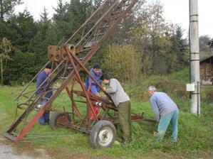 Chlapi pripravujú rebrík, aby vedeli natiahnuť elektrický kábel na stĺp