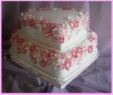 Dvoupatrový svatební dort ve tvaru srdce, zdobený několika desítkami drobných kvítečků; lazeno do bílo-růžové