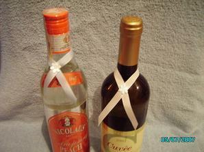 Stužky na flaše, nie je to dobre vidieť ale jedna je modrá s bielou kvetinkou, druhá biela s modrou kvetinkou