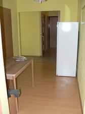 Hala - teď už máme u stolu i židle. Dveře vlevo do dětského pokoje, rovně koupelna a záchod.