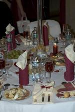 detailný pohľad na stôl, obrúsky s vyšitým našim monogramom (bol v nich ukrytý príbor), hostia si ich po svadbe vzali domov na pamiatku, na vrchu položený program hostiny, KirRoyal (šampanské s likérom z čiernych ríbezlí) s jahodou, predjedlo prosciu