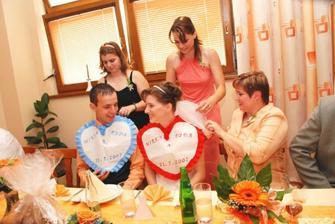 A pro změnu ženichova svědkyně, nevěstina sestra vytvořila novomanželům bryndáky. Připevňuje s nejmladší sestrou.