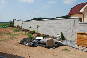 dokončení záhonu podél zdi, všude už bude jen tráva.. ještě přijdou kamínky kolem čistírny, vykukuje Montíka bouda