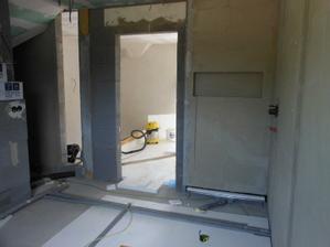 Vpravo sprchovy kut, dvere do chodby a vedla nich miesto na sklobeton
